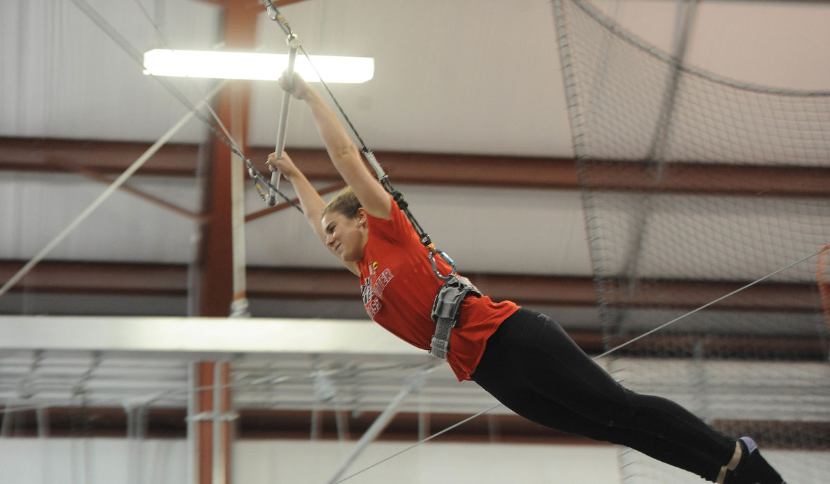 Female student flying through the air during trapeze school
